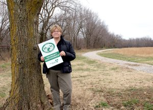 Allyson Ransom, who wrote the grant request for the Pop Allum Park trail, stands near where the new trailhead will be located. The existing trail, shown in the photo along with a connecting loop, will be upgraded and paved.