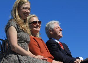 2011| Former President Bill Clinton seated with his wife, Sec. of State Hilary Clinton, and their daughter, Chelsea Clinton, at the Clinton Park Bridge dedication ceremony.