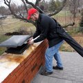 Kevin Mansell, an inspector and technician with Top Hat Services, removes a chimney cap to clean the...