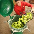 Jared Ward, co-owner of Ozark Tennis Academy, loads used tennis balls into a Green Tennis Machine to...