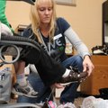 Twila Butler, a family specialist with Benton County Public Schools, helps a child try on shoes Frid...