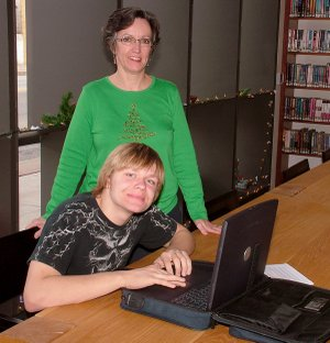 Joshua Harrington tries out a refurbished laptop computer at the Gentry Public Library on Dec. 22 while Gentry librarian Darla Threet looks on.