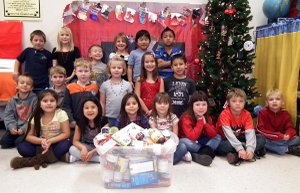 Janet Barkley's first-grade class posed with food they earned with home chores.