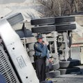 A trooper examines an overturned gravel truck Wednesday.
