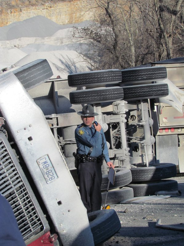 A trooper examines an overturned ...