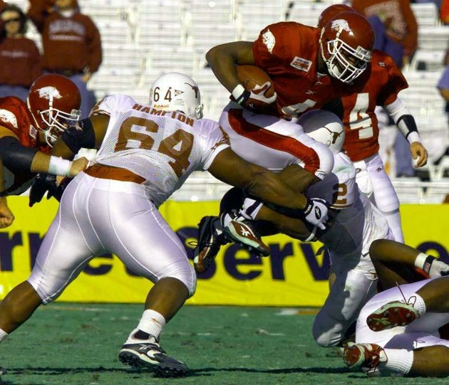 file-arkansas-running-back-cedric-cobbs-jumps-over-texas-defenders-casey-hampton-64-and-montrell-flowers-in-the-2000-cotton-bowl-a-27-6-razorbacks-victory