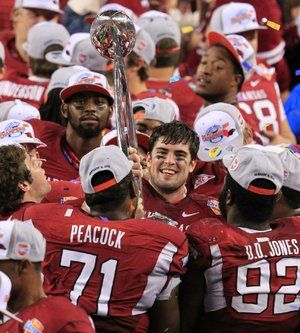Arkansas defensive MVP, Jake Bequette holds up the Cotton Bowl trophy with team mates after defeating Kansas State 29-16 at Cowboys Stadium.