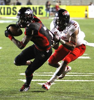 Northern Illinois wide receiver Martel Moore (1) tries to escape the tackle of Arkansas State defensive back Don Jones (5) after a reception in the second half of the Huskies' 38-20 victory in the GoDaddy.com Bowl on Sunday night.