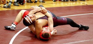 Gentry senior Ricky Hernandez works to pin his Northside High School opponent on Thursday in Gentry's Carl Gym. Hernandez won the match and Gentry picked up a team win.