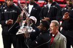 Arkansas football players Cobi Hamilton and Tenarius Wright (center) and Coach Bobby Petrino hold up the Cotton Bowl trophy during halftime of Arkansas' basketball game against Michigan on Saturday at Walton Arena in Fayetteville.