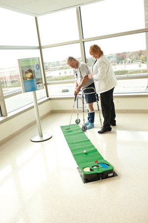 The Joint Replacement Center's program coordinator, Karen Tanner, helps a patient play golf, which is part of group therapy.