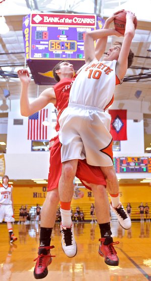 Mark Gathright of Dardanelle High School attempted to block a shot by Gravette High School's Terence Pierce in play against Ozark High School in Ozark on Feb. 22. The Lions of Gravette beat the Dardanelle Lizards in overtime, 62-61.