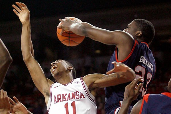 Mississippi's Reginald Buckner blocks a shot by Arkansas' BJ Young in the first half Tuesday in Fayetteville. Buckner had three of the Rebels' seven blocks in a 77-75 victory.