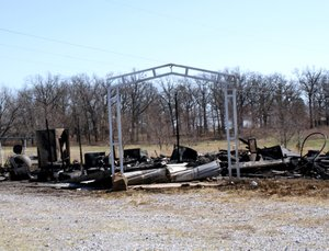 Support columns for a carport are all that remain standing following a fire that destroyed a frame home at Beaty Road last Thursday shortly after noon. The blaze, which is still under investigation by the sheriff's department, was prevented from spreading to nearby homes by three fire departments.