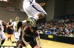 Arkansas Democrat-Gazette/RICKMCFARLAND --03/01/12-- Junction City's Jamario Bell jumps over E. Poinsett's Darius Barnes in their 2A State Finals Basketball tournament game Thursday in Hot Springs.