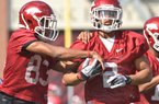 University of Arkansas receivers Maudrecus Humphrey (left) and Julian Horton run drills during the Razorbacks first spring practice at Razorback Stadium in Fayetteville.