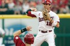 Arkansas second baseman Bo Bigham turns a double play at second over Alabama's Jared Reaves during Sunday's game at Baum Stadium in Fayetteville.