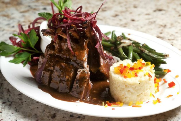 the-dijon-garlic-encrusted-colorado-lamb-rack-comes-with-sauteed-haricot-verts-and-a-rice-cake-at-arthurs-prime-steakhouse