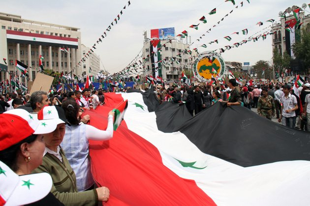 pro-syrian-government-demonstrators-carry-a-giant-national-flag-at-a-rally-at-sabe-bahrat-square-to-commemorate-the-65th-anniversary-of-the-foundation-of-the-ruling-baath-arab-socialist-party-in-damascus-syria-saturday-april-7-2012-syrian-president-bashar-assad-has-accepted-a-cease-fire-deadline-brokered-by-international-envoy-kofi-annan-which-calls-for-his-forces-to-pull-out-of-towns-and-cities-by-tuesday-and-for-both-government-and-rebels-to-lay-down-their-arms-by-6-am-local-time-thursday