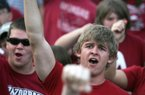 Tyler Grant, a freshman at the University of Arkansas, joins fans in a Hog call during a rally Monday in support of head football coach Bobby Petrino at The Gardens on the Fayetteville campus.