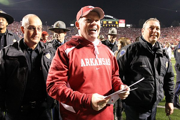 Arkansas head coach Bobby Petrino smiles as he leaves the field after their victor over LSU during the LSU v. Arkansas game held at War Memorial Stadium on Saturday.