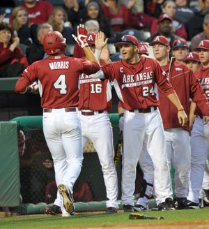 Arkansas Democrat-Gazette/MICHAEL WOODS --04/13/2012-- Arkansas center fielder Jacob Morris is congratulated by teammates after scoring a run in the third inning of Friday night's game against Kentucky at Baum Stadium in Fayetteville.