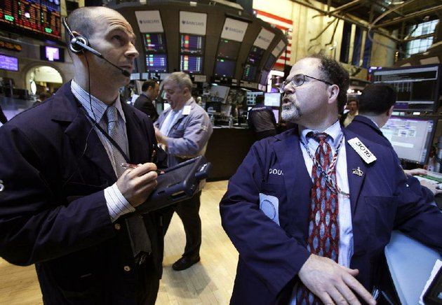 specialist-douglas-johnson-right-works-at-his-post-on-the-floor-of-the-new-york-stock-exchange-on-monday