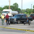 Van Buren police investigators secure a shooting scene Tuesday outside the Fort Smith/Van Buren Welc...