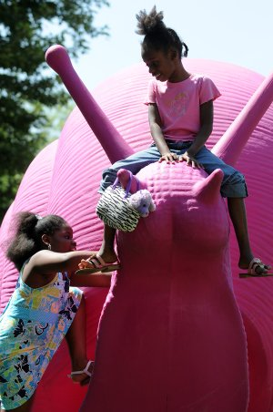 Treasure Deanes, 7, top, and Nia Turner, 9, climb on one of the pink plastic snails on display Wednesday in downtown Bentonville. The snails, 11 in all, were created by Cracking Art Group and are being sponsored by 21c Musuem Hotels. They will be on display through the end of June to coincide with ArtsFest.