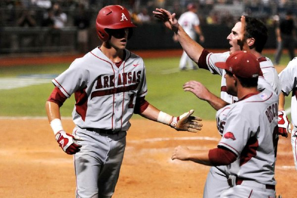Arkansas freshman right fielder Brian Anderson (left) is congratulated by teammates after scoring the lone run in the Razorbacks' 1-0, 10-inning victory over Baylor on Monday in Waco, Texas. Despite finishing 9-9 to end conference play in the regular season and losing their only two games in the SEC Tournament, the Razorbacks have turned things around in the NCAA Tournament and will make their seventh trip to the College World Series in Omaha, Neb.