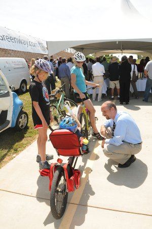 Members of the Stalder family, including Kristen Stalder, left, her brother, Justin, in jump seat, and their mom, Sarah Stalder, rode their bikes to the greenway ground-breaking Tuesday in Rogers. Greg Lindley, chairman of the city's Parks Commission, right, chats with the family during Tuesday's festivities.