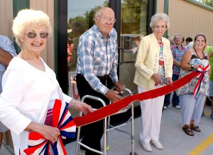 Marion Roberts and Virginia Todd, center, prepare to cut the ribbon at the opening of the new Care and Share store as Betty Howard, left, and Vickie Hearne hold the bright red ribbons.