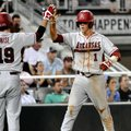 Arkansas' Brian Anderson high-fives Jake Wise after scoring against South Carolina on a single by Ma...