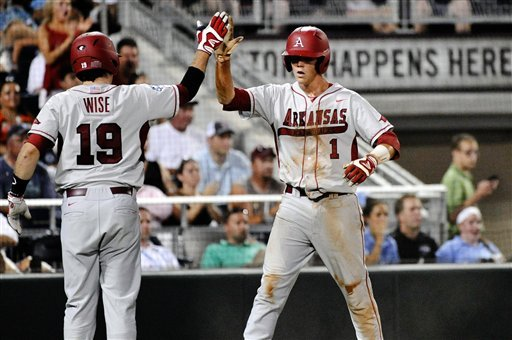 Arkansas' Brian Anderson high-fives Jake Wise after scoring against South Carolina on a single by Matt Vinson in the fourth inning of an NCAA College World Series baseball game in Omaha, Neb., Monday, June 18, 2012. (AP Photo/Ted Kirk)