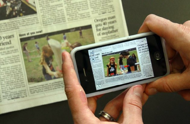 plus-scan-this-photo-for-more-content-starting-july-1-some-photographs-in-the-arkansas-democrat-gazette-will-be-the-portal-to-extra-content-seen-with-many-apple-and-android-mobile-devices-this-photo-shows-a-video-running-and-the-photo-itself-triggers-a-video-when-scanned-with-a-device-loaded-with-the-free-app-arkansas-democrat-gazette-plus