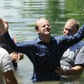 Chad Beardsley of Farmington rejoices June 16 after being baptized during a camp meeting revival at ...
