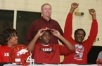 Former White Hall football player Jeremy Sprinkle (seated, center) committed to Arkansas last year, flanked by his parents, Shelia and Billy Sprinkle (right), and his coach, Mike Vaughn (standing). Sprinkle will begin his college career at tight end, but could possibly see action at several other positions.
