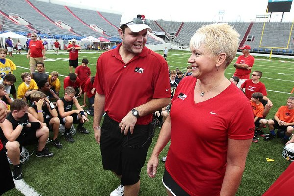 Chase Miller (left) and Michelle Uekman, mother of former Arkansas Razorbacks football player Garrett Uekman. talk to players at the Garrett Uekman 7-on-7 Football Camp on Friday at War Memorial Stadium in Little Rock. Miller, a former high school teammate, helped pitch the idea for the Garrett Uekman Memorial tournament.