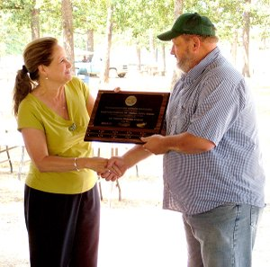 Mary Walter, Occupational Safety and Health Administration Voluntary Protection Programs coordinator, presents a plaque Friday to Terry Smith, manager of the Cargill hatchery in Gentry for being one of 50 company sites in the state to be VPP certified.