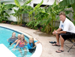 "Tom Smith and four young swimmers enjoying the banana ""tropical paradise"" at the Smith home in Gravette. Swimmers, from the left, are Camille Smith, friends Hannah Frakes and Jessica Bookout and sister Cate Smith."