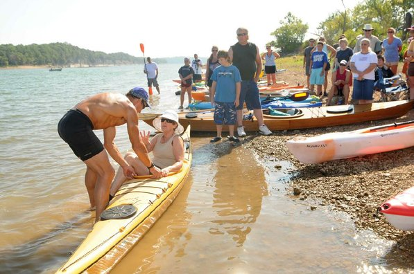 A volunteer helps Herbert show one way to get seated in a kayak.