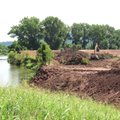 A track hoe clears the ground in preparation for repair of an 800-foot gap in Fort Smith's levee on ...