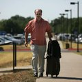 John Vettraino of Detroit pulls his luggage toward the terminal at Northwest Arkansas Regional Airpo...