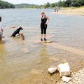 Calvin Schaefer and Sarah Huntsman let their dogs cool off walking on ruins at Monte Ne that are eme...