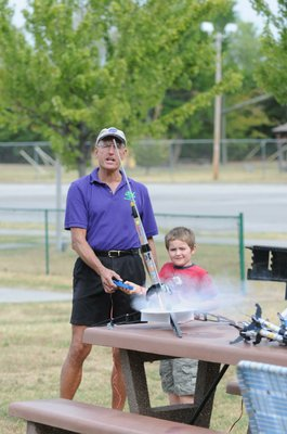 Stephen Cox with Mad Science of Arkansas finishes counting down as a student pushes the button and watches the Estes Rockets he made take off.