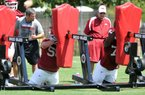 Arkansas Coach John L. Smith (right) and offensive line coach Chris Klenakis (left) watch newcomers during Thursday's opening day workouts at the school's intramural fields.