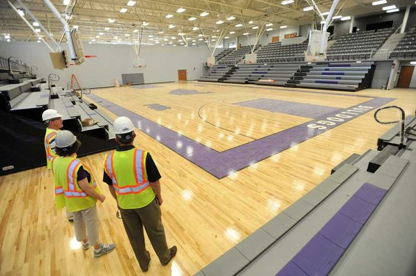 Photo by Andy Shupe—                                                                                        Officials walk through the gymnasium Thursday, Aug. 3, 2012, during a tour of the additions to the Fayetteville High School building.