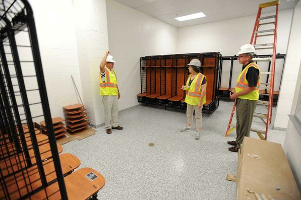 Photo by Andy Shupe—                                                                                        Officials walk through the locker rooms Thursday, Aug. 3, 2012, during a tour of the additions to the Fayetteville High School building.