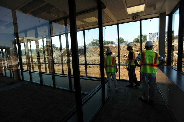 Photo by Andy Shupe—                                                                                        Officials walk through the offices Thursday, Aug. 3, 2012, during a tour of the additions to the Fayetteville High School building.
