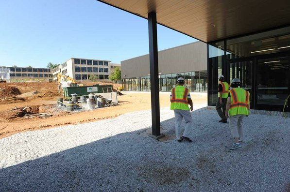 Photo by Andy Shupe—                                                                                        Officials walk through the courtyard Thursday, Aug. 3, 2012, during a tour of the additions to the Fayetteville High School building.